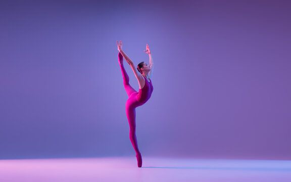 Freedom. Young and graceful ballet dancer isolated on purple studio background in neon light. Art, motion, action, flexibility, inspiration concept. Flexible caucasian ballet dancer, weightless jumps.