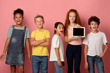 Happy diverse schoolchildren holding tablet computer with empty screen on pink background, mockup for design