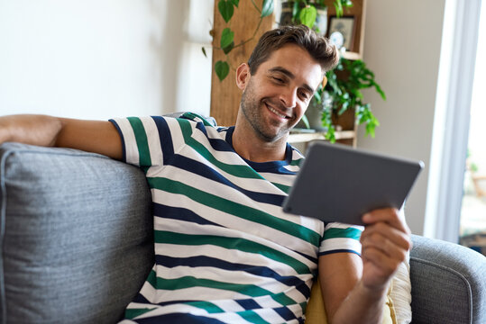 Smiling young man sitting at home using a digital tablet