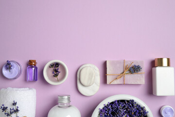 Cosmetic products and lavender flowers on lilac background, flat lay. Space for text