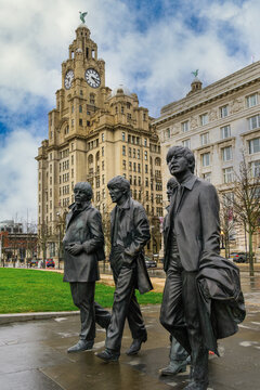 The Beatles statue, bronze art depicting the famous band facing river Mersey with Royal Liver Building in the background, Liverpool, Merseyside, England