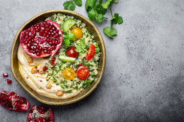 Rustic bowl with couscous salad with vegetables, hummus and fresh cut pomegranate. Middle eastern or Arab style meal with seasonings and fresh cilantro. Healthy Mediterranean dinner, space for text.