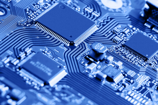 Electronic circuit board close up. Blue background.