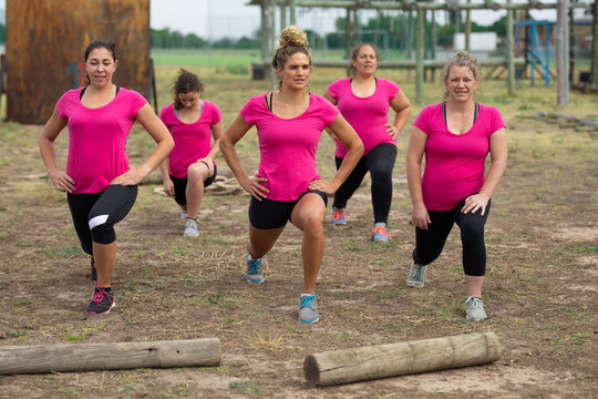 Group of woman performing stretching exercise at boot camp