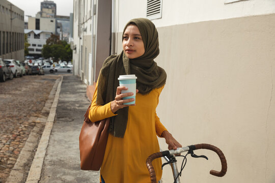 Woman in hijab holding coffee cup while walking with bicycle on street