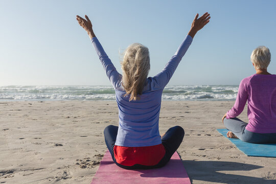 Rear view of woman practicing yoga on the beach