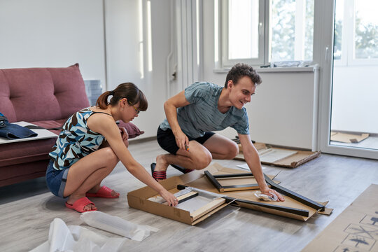 Young couple assembling their furniture