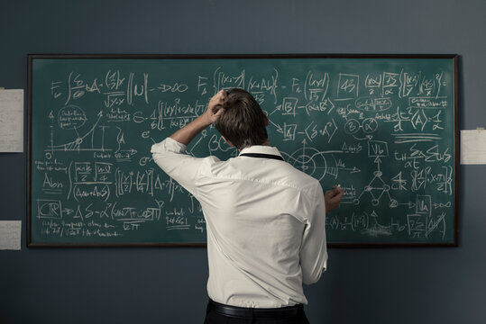 Mathematician solving problems and writing formulas on the chalkboard