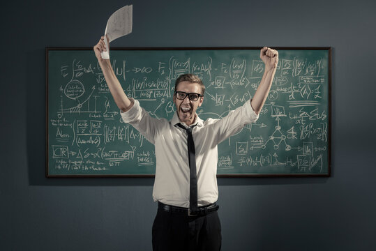 Cheerful successful mathematician solving a problem and celebrating