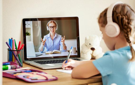 Girl listening to friendly teacher during online lesson.