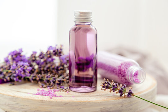 Lavender liquid. Bath cosmetics products in bottles on white wooden rustic board, fresh lavender flowers, soap, bath beads. Lavender essential oil, natural spa products. Aromatherapy treatment