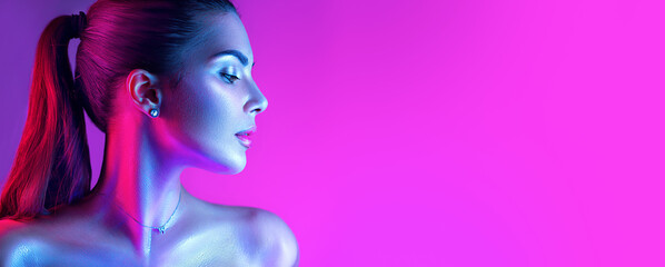 Colorful portrait of a beautiful young woman over purple background. High Fashion model girl in colorful bright neon lights posing in studio, night club. Portrait of beautiful girl in UV. Art design