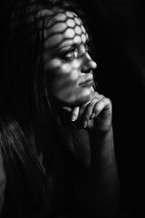 Beautiful woman confesses in the confessional, black and white. Praying woman, fine art portrait with interesting ligth and shadow pattern. Absolution.