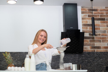 Young woman standing in the kitchen at home and cooking with enjoyment bakery products of flour, milk, cocoa, sugar and fruits. Funny portrait of happy girl chef sifts flour