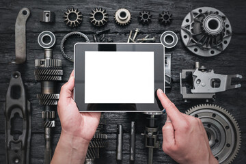 Car service worker is holding a blank screen digital tablet above spare parts background. Car spare...