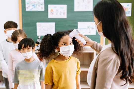 Group of Elementary School Pupils with face mask stood in line let the teacher check, scan thermometer temperature for fever against the spread virus in classroom after covid-19 quarantine.