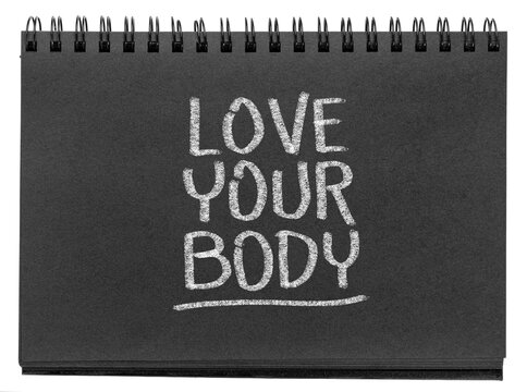 love your body - white chalk inspirational text in a black paper spiral sketchbook, self esteem, acceptance and self care concept