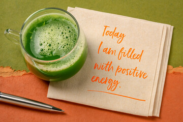 today I am filled with a positive energy - inspirational note on a napkin with a glass of fresh green cucumber juice, lifestyle and positivity concept