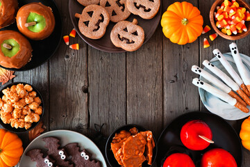 Rustic Halloween treat frame over a dark wood background with copy space. Overhead view. Selection of candied apples, cookies, candy and sweets.