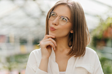 Pensive girl in glasses thinking about something on blur background. Pretty white lady posing in...