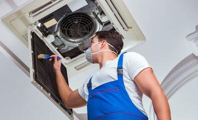 Fototapeta Worker repairing ceiling air conditioning unit