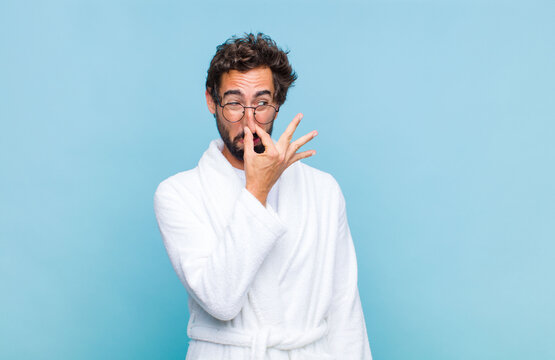 young bearded man wearing a bath robe feeling disgusted, holding nose to avoid smelling a foul and unpleasant stench