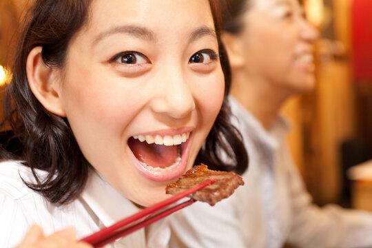焼肉を食べる女性