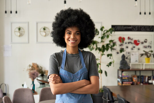Happy African American young woman with Afro hair modern cafe small business owner, female waitress in reopened restaurant looking at camera standing arms crossed in cozy cafe interior. Portrait.