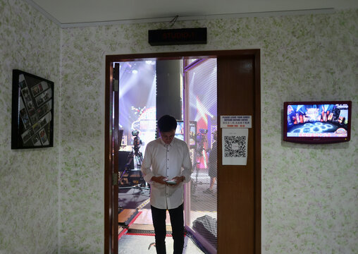 Lex(s) Entertainment's getai organiser Aaron Tan offers incense before a live streaming getai show at a studio in Singapore