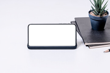 Mockup blank screen smartphone in horizontal view on white table, copy space.