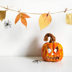 Halloween ceramic pumpkin jack lantern and floral garland on table wall background