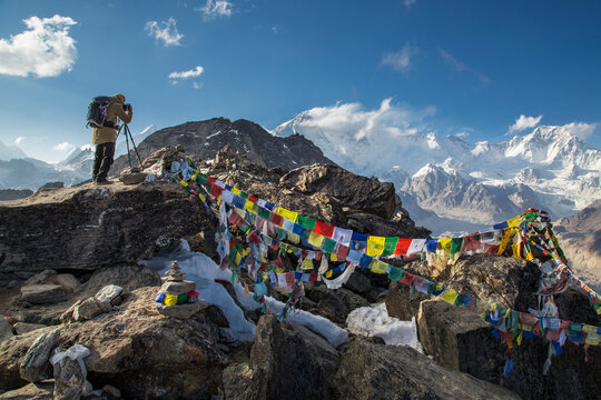 A photographer with a backpack stands on top of a mountain and shots the mountains around. Prayer flags are on the stones. Snow-capped peaks are on the background. Blue sky with a few clouds.
