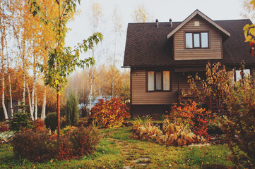 autumn wooden country house and garden view
