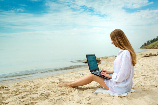 Freelancer workplace on the sea beach. Young woman working travel from outdoor office in nature. Traveler girl with laptop. Successful female business.