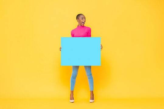 Excited pretty African American woman holding blue paper board with empty space for text on yellow isolated studio background