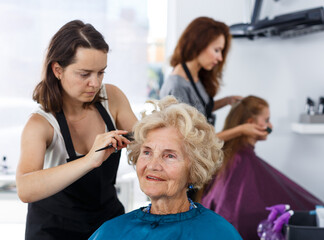 Skilled woman hairdresser making hairstyle for elderly female client in hair studio..
