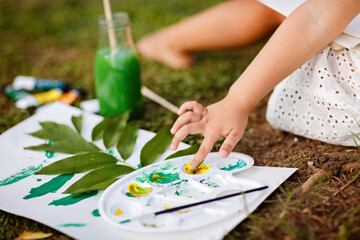 Cute little caucasian kid girl drawing or painting with colored paints in park. Kindergarten children education, back to school after coronavirus pandemic. Social distancing during covid-19 epidemic