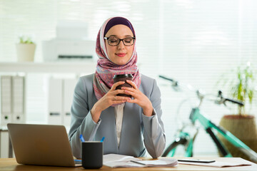 Beautiful young working woman in hijab, suit and eyeglasses sitting in office, smiling. Portrait of confident muslim businesswoman drinking coffee. Modern office with big window,