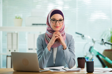 Beautiful young working woman in hijab and suit sitting in office, smiling. Portrait of confident muslim businesswoman. Modern light office with big window.
