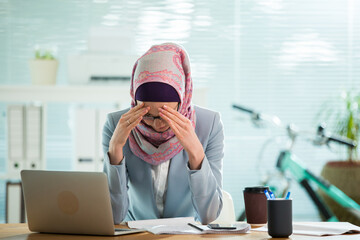 Beautiful young working woman in hijab, suit and eyeglasses sitting in office, having headache. Modern light office with big window.