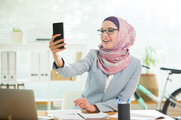 Beautiful young working woman in hijab and suit sitting in office, using smart phone, taking selfie. Portrait of confident muslim businesswoman. Modern light office with big window.