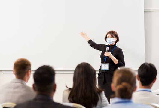 business, education and pandemic concept - smiling businesswoman or teacher in mask with microphone talking to group of students at conference, presentation or lecture and showing something on screen