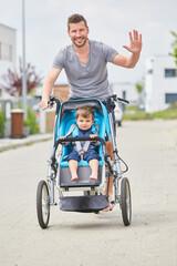 Winkender Vater transportiert sein Kind in der Stadt