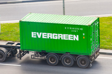 Truck with trailer and green container company Evergreen on city highway. Russia, Saint-Petersburg. 01 august 2020.