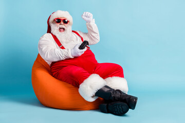 Full length photo of retired old man grey beard joystick crazy win playstation against boss sit beanbag wear red santa x-mas costume suspender sunglass cap isolated blue color background