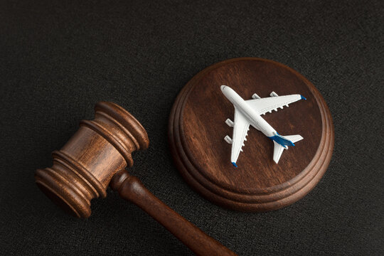 Wooden Judges gavel and toy plane. Aviation Law. To sue the airline.