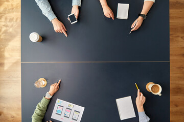 business, people and team work concept - team of startuppers with gadgets and papers pointing fingers to something on office table