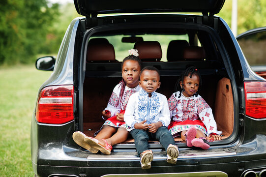 African family in traditional clothes stand against their car, kids sit on trunk.