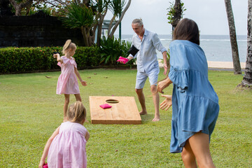 Happy family playing cornhole game by the sea on sunny summer day. Parents and children playing...