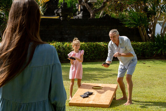 Happy family playing cornhole game outdoor on sunny summer day. Parents and children playing bean bag toss